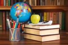 Наука и концепция книг - куча книг и организатора, глобуса на таблице Стоковое Изображение