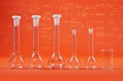 Наука химии - склянки на оранжевой предпосылке Стоковое Изображение RF