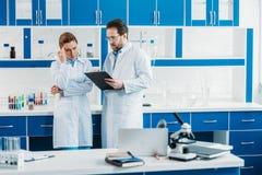 научные исследователя в белых пальто и eyeglasses с блокнотом Стоковое Фото