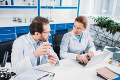 научные исследователя в белых пальто обсуждая работу на рабочем месте Стоковые Фотографии RF