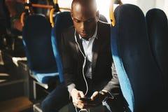 Наушники бизнесмена нося и текстовые сообщения читать на шине стоковое фото