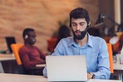 Наушники бизнесмена нося работая на компьтер-книжке в офисе Стоковая Фотография