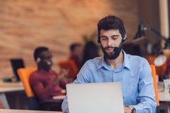 Наушники бизнесмена нося работая на компьтер-книжке в офисе Стоковые Фото