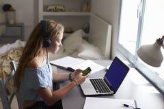 Наушники девушки нося используя smartphone на столе в спальне Стоковая Фотография RF