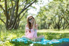 наушники изолировали слушая нот к детенышам белой женщины Сидит на траве в парке, отдыхая наслаждает природой стоковое фото rf
