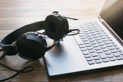 Наушники и клавиатура компьтер-книжки на деревянной доске Стоковое фото RF