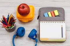 Наушники, карандаши цвета, желтая коробка для завтрака, яблоко и открытая тренировка Стоковые Изображения