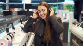 Наушники красивой женщины испытывая в современном магазине сток-видео