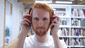 Наушники молодого человека нося, который нужно слушать музыка видеоматериал