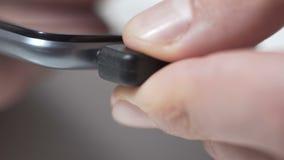 Наушники персоны соединяясь к шлицу на smartphone, пункте обслуживания для устройств сток-видео