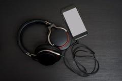 Наушники размера Ull соединяются к мобильному телефону Стоковое Изображение