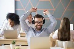 Наушники счастливого бизнесмена нося чувствуя усаживание успеха утехи Стоковое фото RF