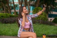 Наушники счастливой молодой женщины нося и принимать фото в парке сидя на обочине Привлекательное женское selfie Стоковые Изображения