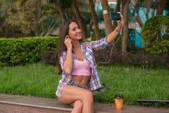 Наушники счастливой молодой женщины нося и принимать фото в парке сидя на обочине Привлекательное женское selfie Стоковое фото RF