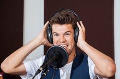 Наушники счастливой мужской певицы нося в студии Стоковая Фотография RF
