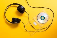 Наушники с диском КОМПАКТНОГО ДИСКА на желтом цвете Стоковые Фото