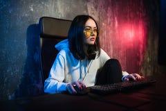 Наушники gamer девушки нося играя игры сети подготавливая участвовать в международных конкуренциях в esports стоковые фото