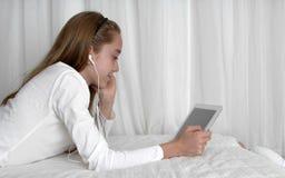 Наушник девушки подростка нося играя на таблетке Стоковые Фотографии RF