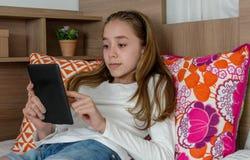 Наушник девушки подростка нося играя на таблетке Стоковое Фото