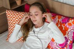 Наушник девушки подростка нося играя на таблетке Стоковые Изображения