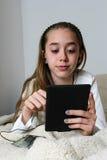 Наушник девушки подростка нося играя на таблетке Стоковая Фотография