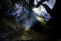 Национальный парк Phong Nha Ke/Вьетнам, 15/11/2017: Подсвеченное положение женщины на утесе внутри пещеры Tien вида в Phong Nha K стоковое фото rf