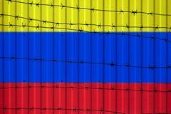 Национальный флаг Колумбии на загородке Колючая проволока на переднем плане символизирует запрет или запрет входа для пересекая г Стоковые Фото