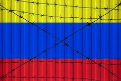 Национальный флаг Колумбии на загородке Колючая проволока на переднем плане символизирует запрет или запрет входа для пересекая г Стоковые Фотографии RF