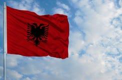 Национальный флаг Албании на флагштоке перед голубым небом Стоковые Фотографии RF