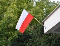 Национальный флаг Польши повешен вне на фасаде здания Стоковые Фотографии RF