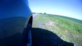 Начала автомобиля двигая от обочины шоссе в солнечном летнем дне Камера установлена на стороне автомобиля видеоматериал