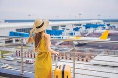 Начало ее путешествия Красивое ltraveler молодой женщины в желтом платье и желтом чемодане ждет ее полет стоковые фотографии rf