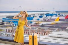 Начало ее путешествия Красивое ltraveler молодой женщины в желтом платье и желтом чемодане ждет ее полет стоковые изображения rf
