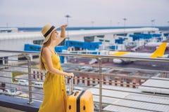 Начало ее путешествия Красивое ltraveler молодой женщины в желтом платье и желтом чемодане ждет ее полет стоковое изображение