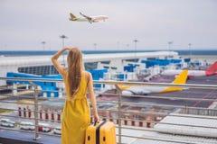 Начало ее путешествия Красивое ltraveler молодой женщины в желтом платье и желтом чемодане ждет ее полет стоковая фотография