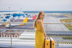 Начало ее путешествия Красивое ltraveler молодой женщины в желтом платье и желтом чемодане ждет ее полет стоковые изображения