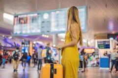 Начало ее путешествия Красивое ltraveler молодой женщины в желтом платье и желтом чемодане ждет ее полет стоковое фото rf