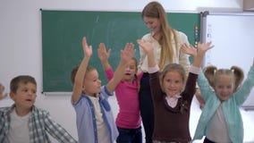 Начальная школа, группа в составе руки потехи детей скача и развевая близко к учителю на предпосылке доски