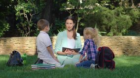 Начальная школа, маленький школьник и школьница с женщиной учителя прочитали учебник и болтовню во время урока акции видеоматериалы