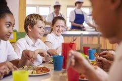 Начальная школа ягнится на таблице в школьном кафетерии, конце вверх стоковые изображения rf