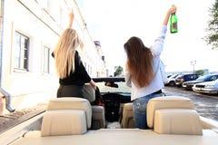 Начинать новое путешествие с шампанским 3 красивых молодых жизнерадостных женщины смотря один другого с улыбкой и выпивать Стоковая Фотография RF