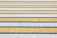 Нашивки пешеходного перехода белые и желтые на асфальте Стоковые Изображения RF