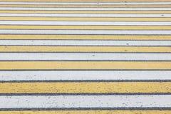 Нашивки пешеходного перехода белые и желтые на асфальте Стоковая Фотография RF