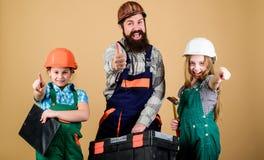 Наш папа имеет умелые пальцы Сестры помогают построителю отца Домашняя реновация Создайте комнату вы действительно хотите в реаль стоковые фотографии rf