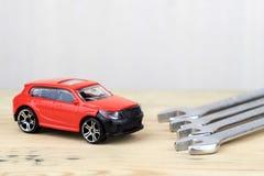 На автомобиле игрушки светлой деревянной предпосылки красном рядом с которым ключи стоковое фото