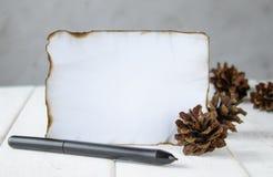 На белых деревянных досках, лист бумаги, который сгорели на краях, конусах леса, черной ручке на краях Выходить космос для текста стоковые фото