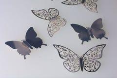На белых поверхностных украшениях лож сделанных бабочек отрезать от фольги Стоковые Изображения