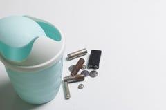 На белизне поверхность пластичный мусорный ящик Рядом с ним ложь используемые батареи Стоковое фото RF
