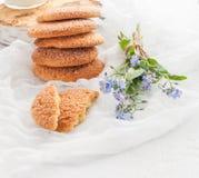 На белой таблице, песочных круглых печеньях, одном сломленном и букете Стоковая Фотография RF