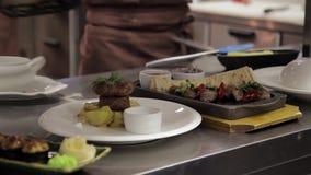 На блюдах переднего плана готовых для таблицы установите в ресторан Служат кашевар, который сток-видео